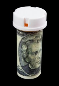 Pill bottle wrapped with 1 twenty dollar bill
