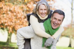 Happy couple. Woman getting a piggy back ride from husband as they stroll in the park