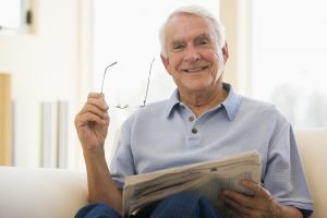 Man reading newspaper with glasses in hand