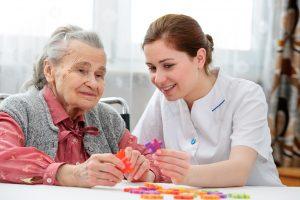 Elder nurse at hospice playing jig saw