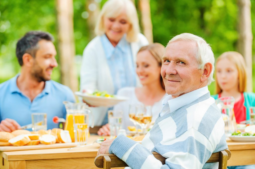 Senior man smiling enjoying time with family
