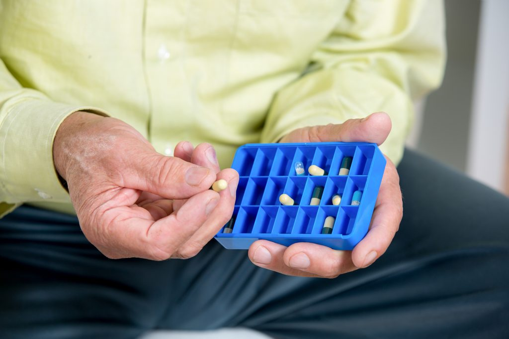 Senior man holding a blue prescription drug organizer