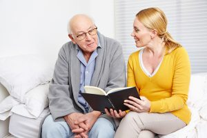 Reading to an elderly staying with elder care facilities