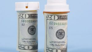Two pill bottles of money representing costs for Medicare Part D