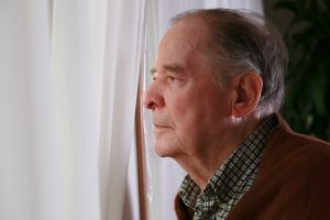 Senior standing male by window with serious depression look