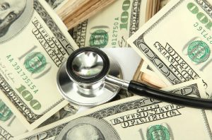 Health care costs concept: stethoscope and dollars background