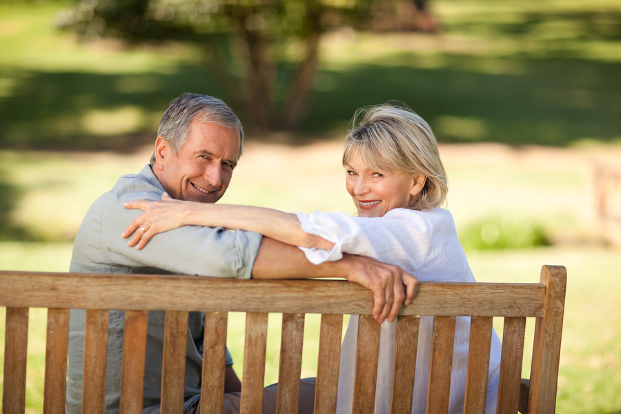 Happy retired couple sitting on the bench , talking about the savings they made for retirement costs