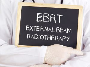 A doctor showing External Beam Radiation therapy written in a black background for the treatment of Skin Cancer