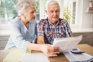 Worried Senior couple checking healthcare bill